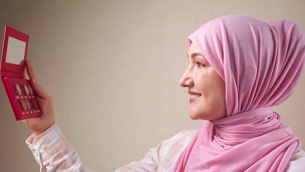 Giovane donna musulmana in hijab che si trucca con un pennello guardandosi allo specchio