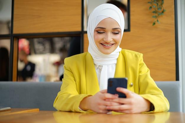 Giovane donna musulmana in hijab usando il suo smartphone in cafe