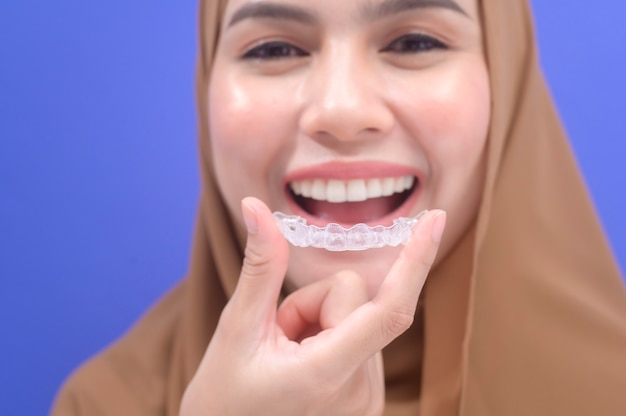 Una giovane donna musulmana che tiene le parentesi graffe invisalign in studio, assistenza sanitaria dentale e concetto ortodontico.