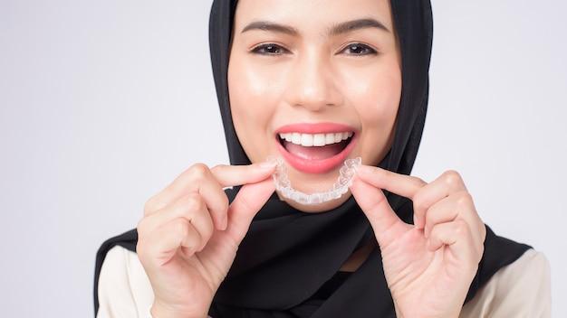 Giovane donna musulmana che tiene bretelle invisalign in studio, assistenza sanitaria dentale e concetto ortodontico.