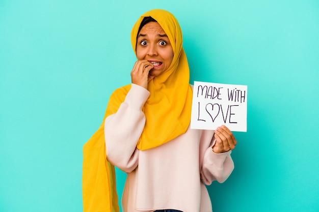 Giovane donna musulmana che tiene un cartello fatto con amore isolato sulle unghie mordaci della parete blu, nervoso e molto ansioso.