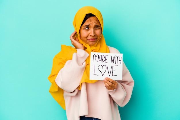 Giovane donna musulmana che tiene un fatto con il cartello di amore isolato sulle orecchie del rivestimento murale blu con le mani.