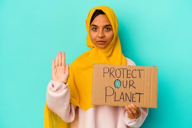 Giovane donna musulmana che tiene un protegge il nostro pianeta isolato su sfondo blu in piedi con la mano tesa che mostra il segnale di stop, impedendoti.