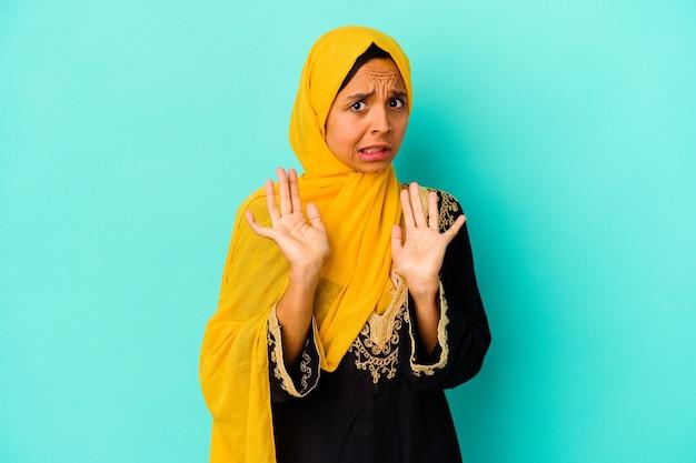 Giovane donna musulmana isolata sulla parete blu che rifiuta qualcuno che mostra un gesto di disgusto