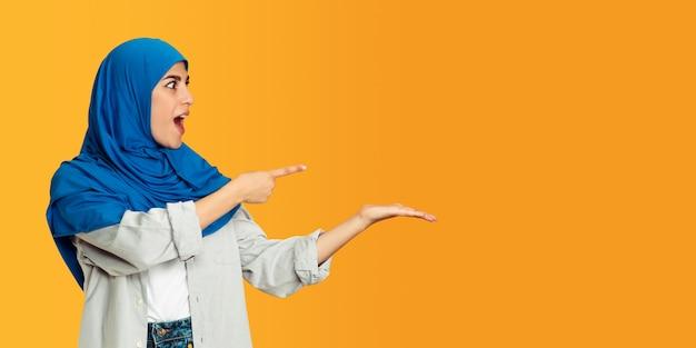 Giovane donna musulmana isolata sulla parete gialla alla moda alla moda bella modella femminile