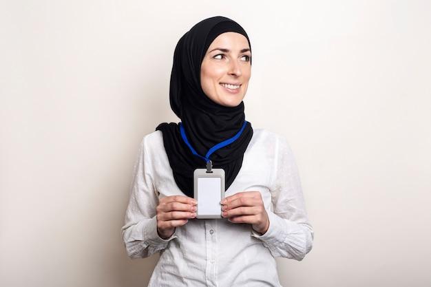 Giovane donna musulmana che indossa una camicia bianca e hijab che mostra il suo badge di ufficio