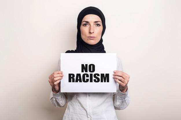 Giovane donna musulmana in camicia bianca e hijab con una faccia triste tiene un foglio di carta bianco
