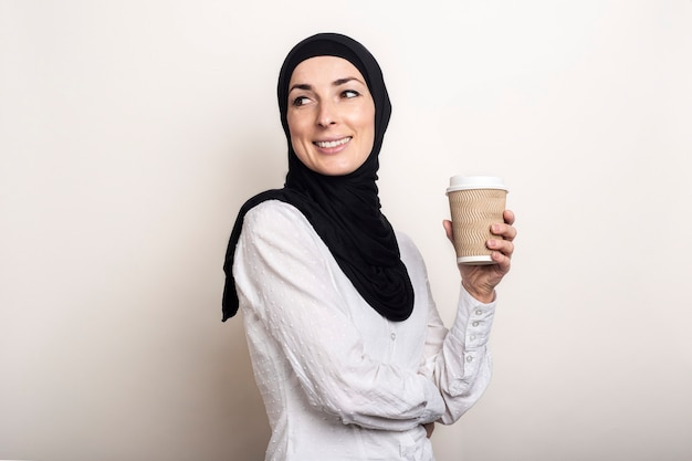 Giovane donna musulmana in una camicia bianca e hijab con un sorriso tiene un bicchiere di carta con il caffè