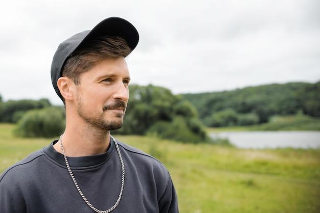 Giovane uomo baffuto in un berretto da baseball all'aperto. ritratto di un ragazzo che guarda al lato
