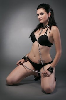 Giovane donna nuda in catena su sfondo nero