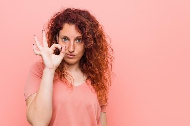 Giovane donna naturale e autentica rossa allegro e fiducioso mostrando gesto ok.