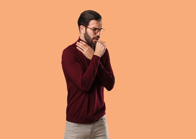 Giovane uomo naturale che tossisce, malato a causa di un virus o di un'infezione