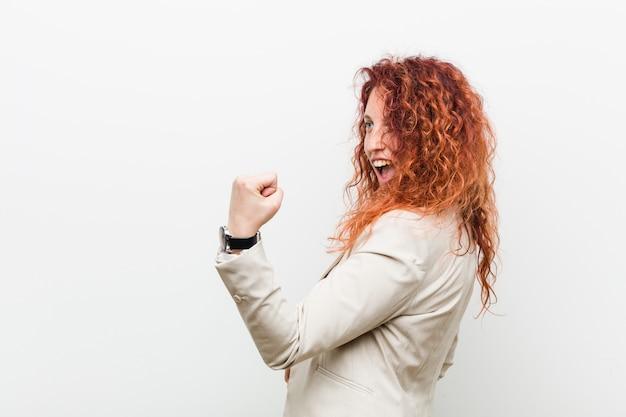 Giovane donna naturale di affari della testarossa che alza pugno dopo una vittoria