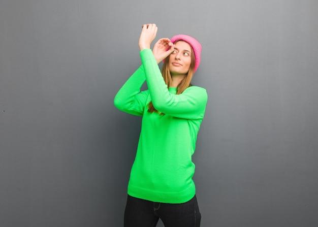 Giovane donna russa naturale che fa il gesto di un cannocchiale