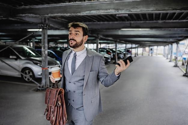 Il giovane uomo d'affari nervoso cammina nel parcheggio e corre sul lavoro.