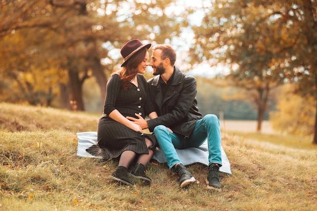Giovane bella coppia nella stagione autunnale nel parco con un momento carino