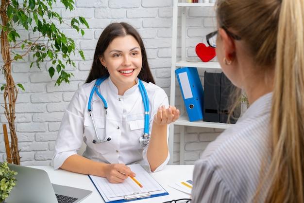 Giovane medico piacevole della donna che ha una conversazione con il suo paziente in ospedale