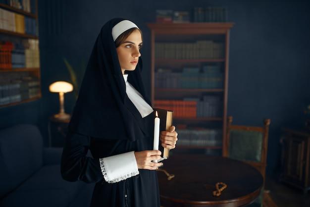 La giovane suora in una tonaca tiene un libro e una candela. la suora si sta preparando per la preghiera nel monastero, religione e fede, persone religiose