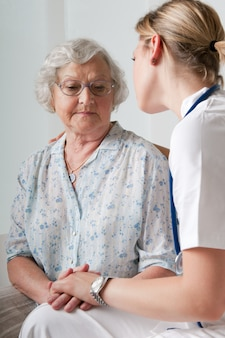 Giovane infermiera consolante e prendersi cura del paziente anziano in ospedale