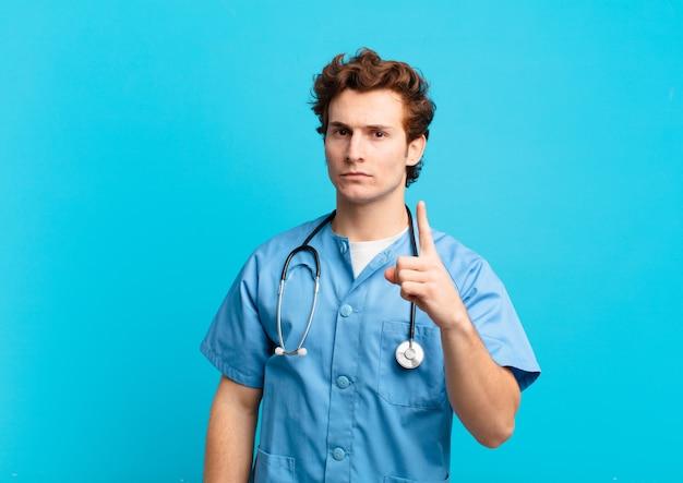 Giovane infermiere che si sente arrabbiato, infastidito, ribelle e aggressivo, lanciando il dito medio, contrattaccando