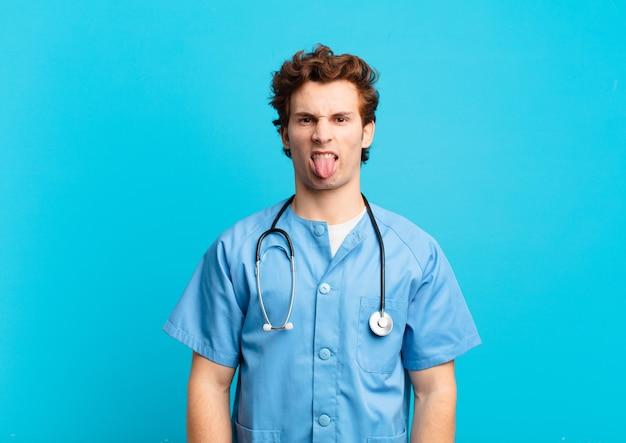Giovane infermiere che si sente disgustato e irritato, tira fuori la lingua, non ama qualcosa di brutto e schifoso