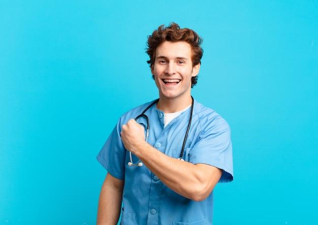 Giovane infermiere che si sente felice, positivo e di successo, motivato quando affronta una sfida o celebra buoni risultati