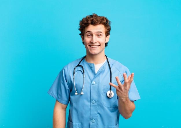 Giovane infermiere che si sente felice, sorpreso e allegro, sorride con atteggiamento positivo, realizza una soluzione o un'idea