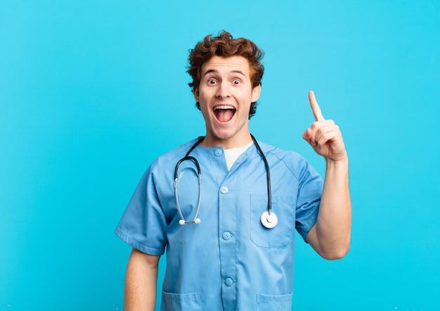 Giovane infermiere che si sente un genio felice ed eccitato dopo aver realizzato un'idea, alzando allegramente il dito, eureka!
