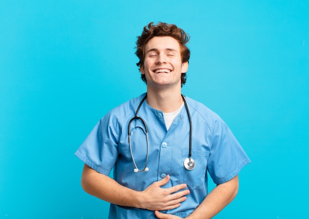 Giovane infermiere che ride ad alta voce per qualche scherzo esilarante, sentendosi felice e allegro, divertendosi