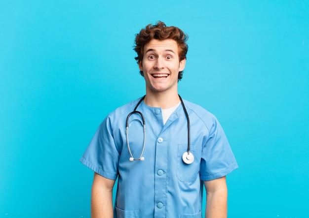 Giovane infermiere che sembra felice e piacevolmente sorpreso, eccitato con un'espressione affascinata e scioccata
