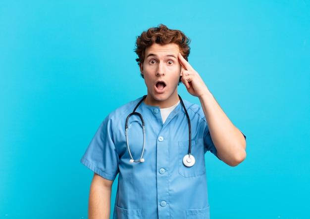 Giovane infermiere che sembra sorpreso, a bocca aperta, scioccato, realizzando un nuovo pensiero, idea o concetto
