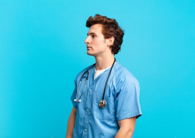 Giovane infermiere in vista di profilo che cerca di copiare lo spazio avanti, pensando, immaginando o sognando ad occhi aperti