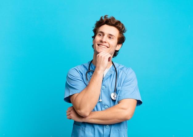 Giovane infermiere che sorride felice e sogna ad occhi aperti o dubita, guardando di lato