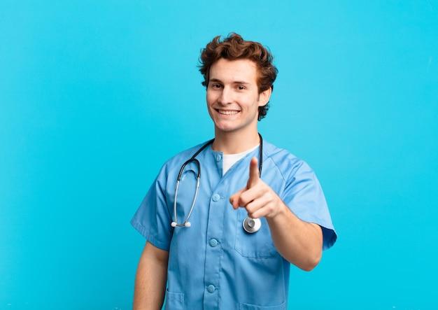 Giovane infermiere che sorride con orgoglio e sicurezza facendo la posa numero uno in modo trionfante, sentendosi un leader