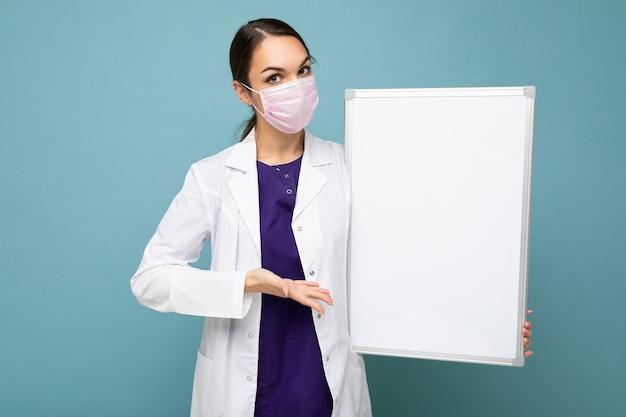 Giovane infermiera in maschera protettiva e camice medico bianco che tiene una lavagna magnetica vuota isolata