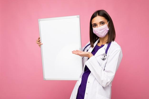 Giovane infermiera in maschera protettiva e camice medico bianco che tiene una lavagna magnetica vuota