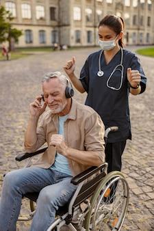 Giovane infermiera in maschera protettiva che si prende cura del paziente anziano in via di guarigione su sedia a rotelle