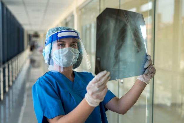 Giovane infermiera in tuta protettiva e schermo facciale che controlla l'immagine dei raggi x del torace, covid19. pandemia