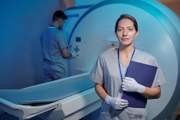 Giovane infermiera in uniforme e guanti in piedi davanti alla macchina medica