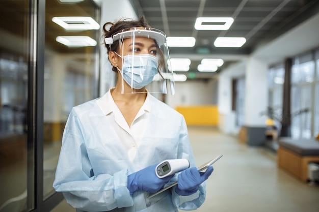 La giovane infermiera che indossa una maschera e una maschera protettiva medica si trova nel corridoio dell'ospedale con un termometro senza contatto e un tablet pronto per testare i pazienti. concetto di assistenza sanitaria e diagnosi.