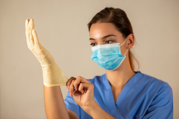 Giovane infermiera con mascherina chirurgica blu che indossa guanti di gomma protettivi.