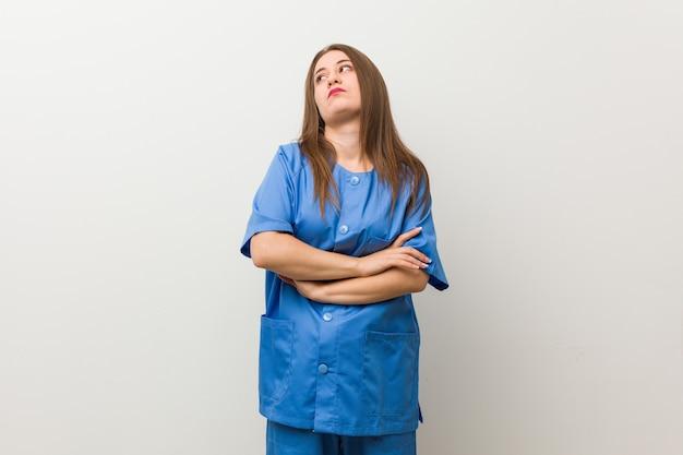 Giovane donna infermiera contro un muro bianco stanca di un compito ripetitivo.