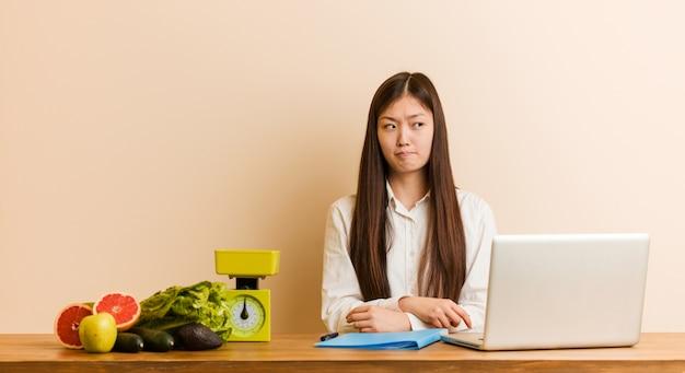 Donna cinese giovane nutrizionista che lavora con il suo computer portatile confuso, si sente dubbioso e incerto.