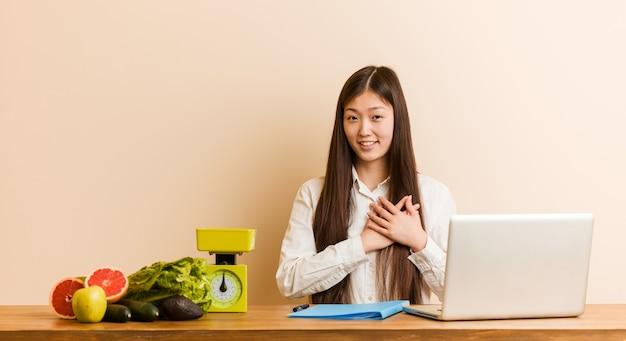 La giovane donna cinese nutrizionista che lavora con il suo laptop ha un'espressione amichevole, premendo il palmo sul petto. concetto di amore.