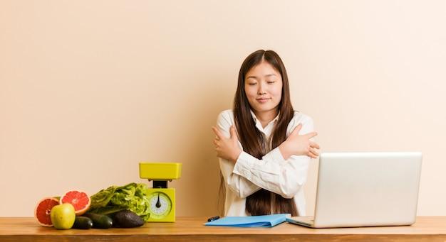 La giovane donna cinese nutrizionista che lavora con il suo laptop si abbraccia, sorridendo spensierata e felice.