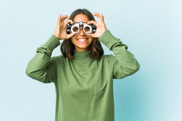 Giovane donna latina oculista eccitata mantenendo il gesto giusto sull'occhio.