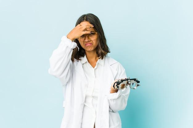 Giovane donna latina oculista con mal di testa, toccando la parte anteriore del viso.