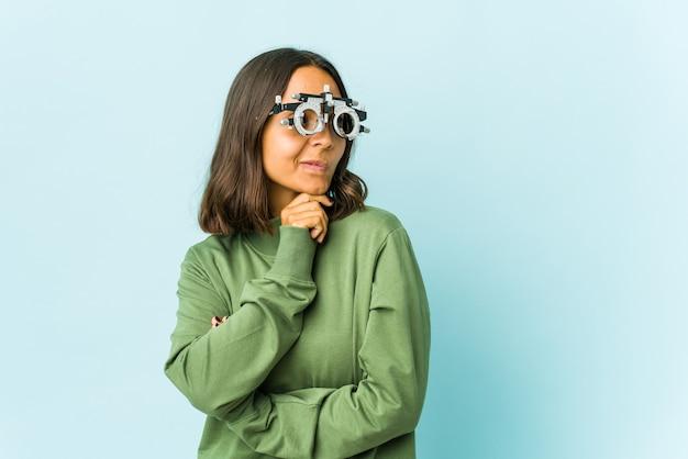 La giovane donna latina oculista sopra il muro isolato confusa, si sente dubbiosa e insicura.