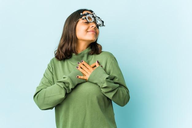 La giovane donna latina oculista sopra il muro isolato ha un'espressione amichevole, premendo il palmo sul petto. concetto di amore.