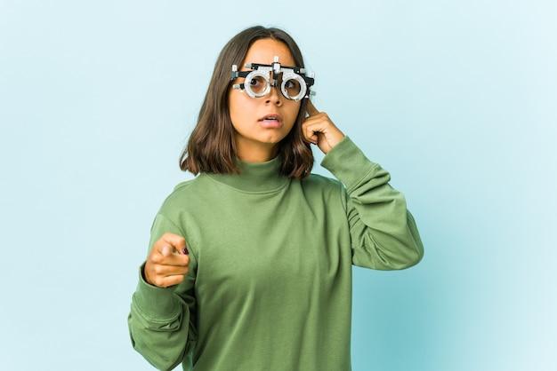 Giovane donna latina oculista che punta il tempio con il dito, pensando, concentrato su un compito.